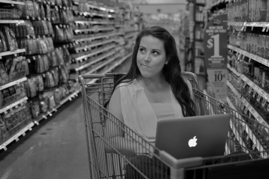 Woman inside a shopping cart with laptop