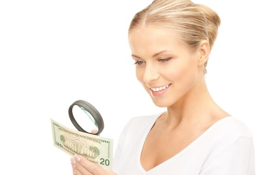 Woman magnifying paper bill